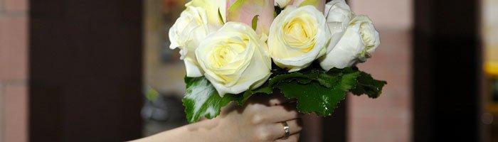 Die Braut hält dem Brautstrauß in der rechten Hand.