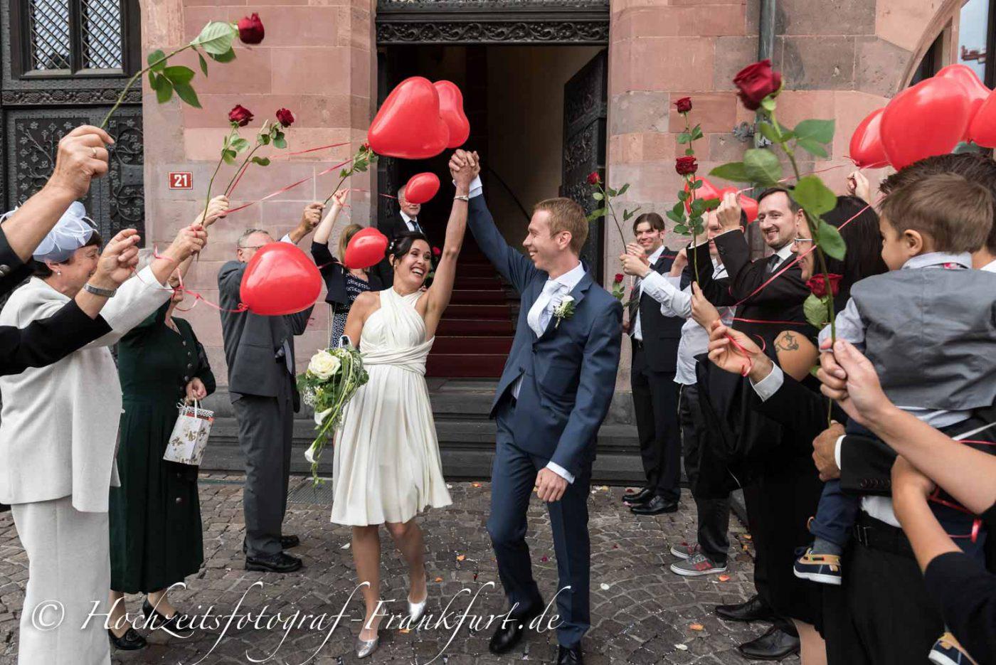 Standesamt Römer in Frankfurt am Main: Hand in Hand. die Hochzeitsgäste stehen mit Rosen Spalier. Das Hochzeitspaar reißt die Arme nach oben.