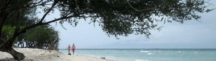 Ein Hochzeitspaar schländert am weißen Strand von Gili Trawangan